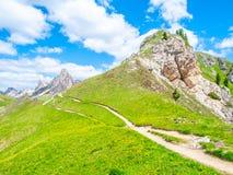 Ландшафт доломитов с зелеными лугами, голубым небом, белыми облаками и скалистыми горами Стоковая Фотография RF