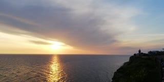 Ландшафт захода солнца моря в тонах сини и золота На поверхности моря солнечный путь сверкнает Маяк стоковые изображения rf