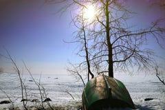 Ландшафт зимы залива во льду и шлюпке на береге стоковые фотографии rf