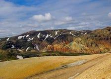 Ландшафт зоны Landamannalaugar геотермической с покрашенными горами риолита, черными полями лавы, снегом и плохой растительностью стоковая фотография