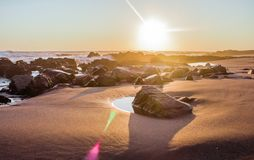 Ландшафт пляжа с утесами во время захода солнца стоковая фотография rf