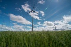 Ландшафт с ветрянками в ветровой электростанции на солнечный день с облаками в небе стоковые изображения