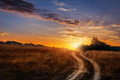 Ландшафт с дорогой колейности на небе захода солнца с предпосылкой солнечного луча стоковые фотографии rf
