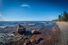 Ландшафт с каменистым берегом на озере на солнечный день Большие камни в воде Бечевник с деревьями стоковые изображения rf