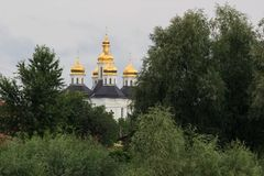 Ландшафт с церковью, облачным небом, солнцем и деревьями ` s Катрина без листьев, в начале Chernigiv -го марша, Украины Стоковые Изображения