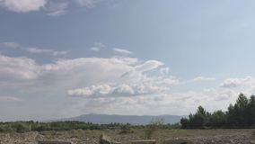 Ландшафт River Valley Каменистый курс, голубые облака На горизонте цепь горы видеоматериал
