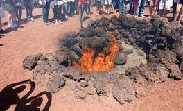 ЛАНСАРОТЕ, ИСПАНИЯ - 20-ОЕ АПРЕЛЯ 2018: Непознаваемые туристы наблюдая и принимая фото демонстрации огня в Timanfaya вулканическо стоковое изображение rf