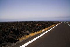 Лансароте - Timanfaya NP: Управлять отключением на бесконечной пустой дороге асфальта между черными утесами лавы в неурожайном ла стоковое изображение