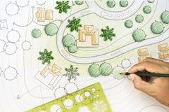 Ландшафтный архитектор конструируя на плане места Стоковые Изображения RF