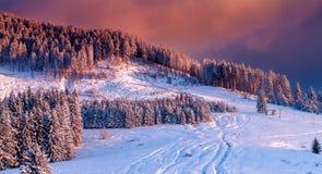 Ландшафт горы в зиме, покрытой с снегом, с красочным заходом солнца который покрывает всю сцену в теплом, фиолетов-апельсин краси