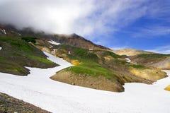 Ландшафт горы с зеленой травой и снежными землями Стоковые Фото