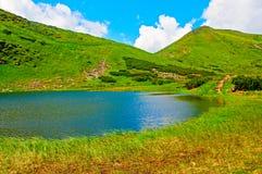 Ландшафт горы с озером и облаками в небе Стоковое фото RF