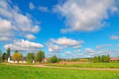 Ландшафт лета голубого неба, белых облаков и зеленого поля Стоковое фото RF