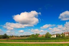 Ландшафт лета голубого неба, белых облаков и зеленого поля Стоковая Фотография