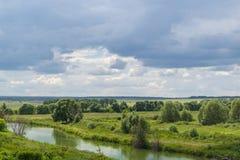 Ландшафт лета зеленых полей и облачного неба сельское место Стоковое фото RF