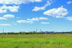 Ландшафт лета с полем травы и промышленных объектов далеко  Стоковая Фотография