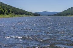 Ландшафт летнего дня с рекой, лесом, облаками на голубом небе и солнцем Стоковое Фото