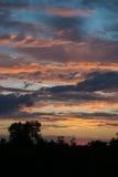 Ландшафт захода солнца с горящим небом полным облаков Стоковые Изображения RF