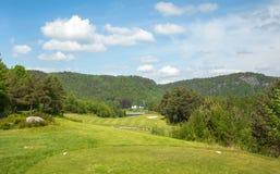 Ландшафт на поле для гольфа Bjaavann с зеленой травой, деревьями, красивым голубым небом, панорамой стоковая фотография rf