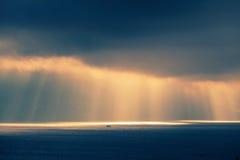 Ландшафт океана, выравнивая солнечный свет в темном небе Стоковая Фотография