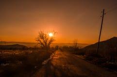 Ландшафт осени или зимы с дорогой и деревьями Заход солнца световых лучей золота На предпосылке гор и неба с облаками Стоковое Изображение RF