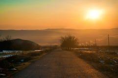 Ландшафт осени или зимы с дорогой и деревьями Заход солнца световых лучей золота На предпосылке гор и неба с облаками Стоковые Изображения