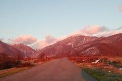 Ландшафт осени или зимы с дорогой и деревьями Заход солнца световых лучей золота На предпосылке гор и неба с облаками Стоковое Фото
