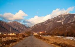 Ландшафт осени или зимы с дорогой и деревьями Заход солнца световых лучей золота На предпосылке гор и неба с облаками Стоковое фото RF