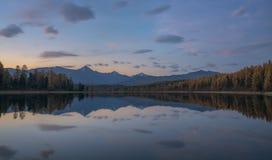Ландшафт осени света захода солнца пинка озера зеркал поверхностный с горной цепью на предпосылке Стоковое фото RF