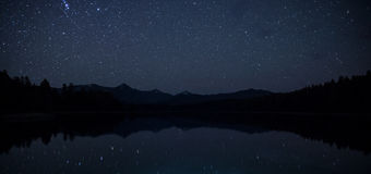 Ландшафт поверхностного озера зеркал захватывающий с горной цепью на ноче с небом с мириадами ярких звезд Стоковые Изображения RF