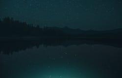 Ландшафт поверхностного озера зеркал захватывающий с горной цепью на Starlit ноче через зеленый фильтр Стоковая Фотография RF