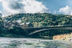 Ландшафт реки с старыми мостом и домами Стоковые Изображения
