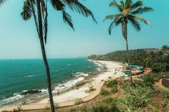 Ландшафт солнечности с длинным лесом песчаного пляжа и ладоней, туристом охлаждая в голубых волнах океана и кафами на взморье Стоковые Изображения RF