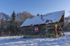 Ландшафт старого покинутого дома фермы покрытого с снегом в морозной зиме Стоковые Изображения