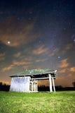 Ландшафт с винтажной деревянной лачугой под звездами освещает Стоковая Фотография RF