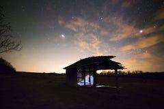 Ландшафт с винтажной деревянной лачугой под звездами освещает Стоковые Изображения RF