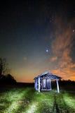 Ландшафт с винтажной деревянной лачугой под звездами освещает Стоковые Фотографии RF