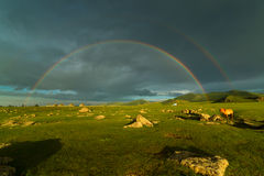 Ландшафт с двойной радугой над широкой лошадью поля и пасти Стоковое Изображение