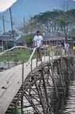 ЛАОС - ФЕВРАЛЬ 2013: Деревянный мост через реку на Vang Vieng, Лаосе Стоковое Изображение RF