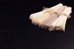 Лапши различных пачек сырцовые на черной striped предпосылке циновки с космосом экземпляра, взгляд сверху стоковые фото