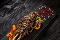 Лапши Soba лапшей гречихи гречихи желтых и красного перца, трав Лотк-Азиатская кухня На каменном подносе на темноте Стоковое Изображение RF