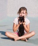 Ласка маленькой девочки с котенком стоковое изображение