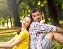 Ласковые молодые пары сидя в парке Стоковая Фотография