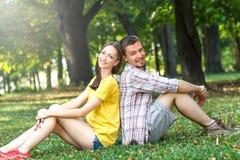 Ласковые молодые пары сидя в парке Стоковое Фото