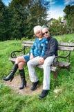 Ласковые пары сидя на скамейке в парке Стоковые Фотографии RF