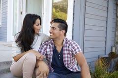 Ласковые пары сидя на шагах вне дома Стоковая Фотография
