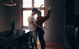 Ласковые пары стоя совместно в кухне Стоковые Изображения