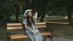 Ласковый человек обнимая его беременную жену в парке сток-видео