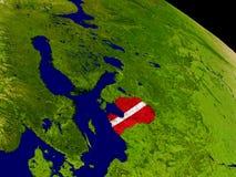 Латвия с флагом на земле Стоковая Фотография