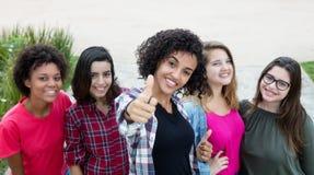 Латино-американская женщина показывая большой палец руки с группой в составе подруги Стоковые Фотографии RF